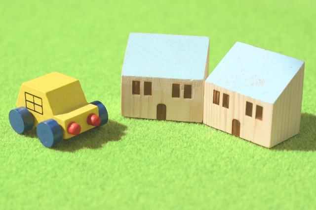 芝の上の木の家と車